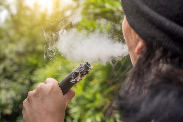 Nahaufnahme eines mannes, der eine elektronische zigarette vaping ist