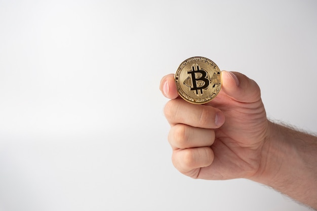 Nahaufnahme eines mannes, der eine goldfarbene bitcoin-münze hält. weißer hintergrund, cryptocurrency-konzept, kopienraum