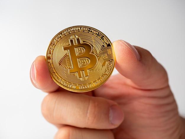 Nahaufnahme eines mannes, der eine goldfarbene bitcoin-münze hält. weißer hintergrund, kryptowährungskonzept