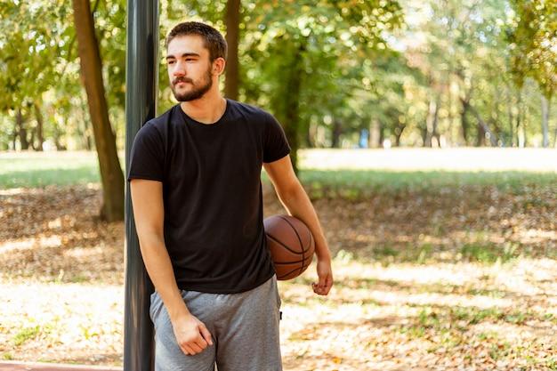 Nahaufnahme eines mannes, der einen basketball hält
