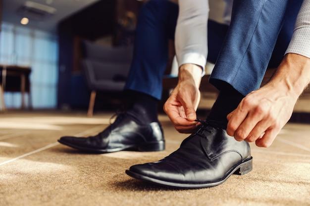 Nahaufnahme eines mannes, der einen schnürsenkel an seinem lederschuh bindet. er bereitet sich auf die arbeit vor.
