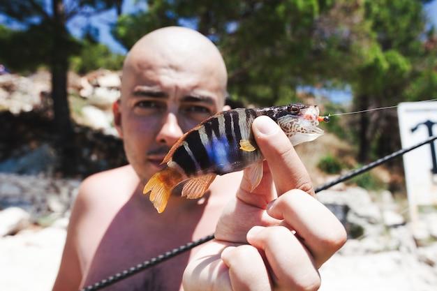 Nahaufnahme eines mannes, der frischen gefangenen fisch anhält