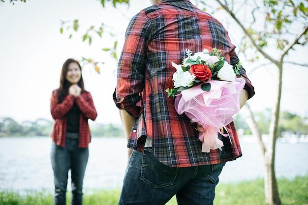 Nahaufnahme eines mannes, der glückliche frauenblumen gibt. ein bild eines romantischen paares erhalten.