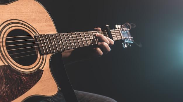 Nahaufnahme eines mannes, der im dunkeln mit bühnenbeleuchtung eine akustikgitarre spielt.