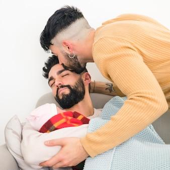 Nahaufnahme eines mannes, der in der hand sein tragendes baby des schlafenden freundes küsst