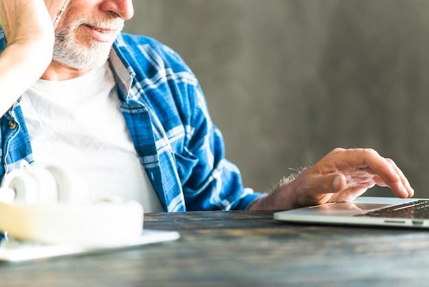 Nahaufnahme eines mannes, der laptop auf dem schreibtisch verwendet