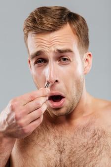 Nahaufnahme eines mannes, der nasenhaare mit einer pinzette entfernt, die auf der grauen wand isoliert ist?