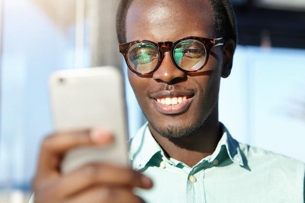 Nahaufnahme eines mannes, der newsfeed über soziale netzwerke mit smartphone durchsucht