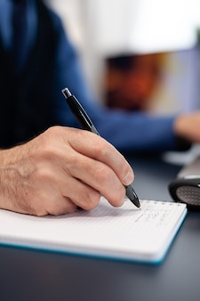 Nahaufnahme eines mannes, der notizen auf dem notebook macht, während er von zu hause aus arbeitet. älterer unternehmer am heimarbeitsplatz mit tragbarem computer am schreibtisch sitzend, während die frau ein buch auf dem sofa liest.