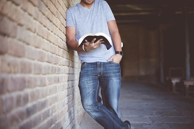 Nahaufnahme eines mannes, der sich an eine wand lehnt, während er die bibel liest