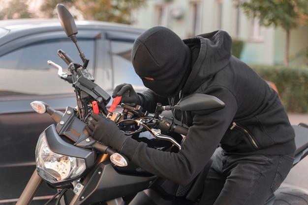 Nahaufnahme eines mannes, der sich darauf vorbereitet, ein motorrad zu stehlen