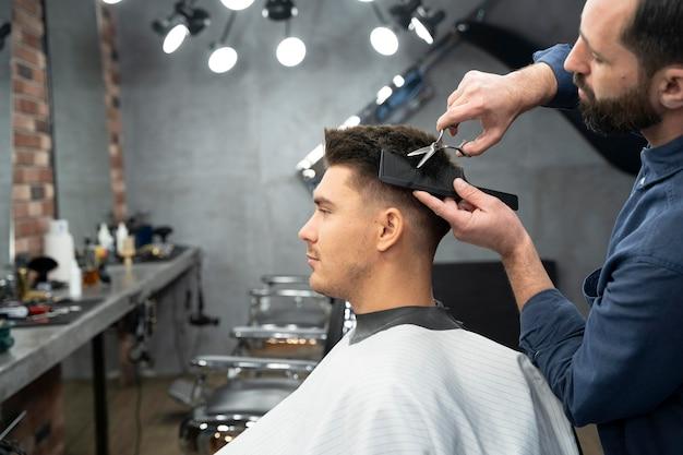 Nahaufnahme eines mannes, der sich die haare schneiden lässt