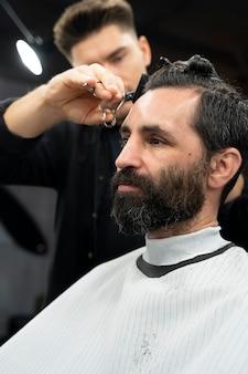 Nahaufnahme eines mannes, der sich im salon die haare schneiden lässt