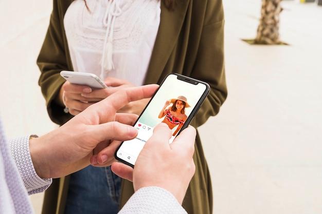 Nahaufnahme eines mannes, der social media-app auf smartphone verwendet