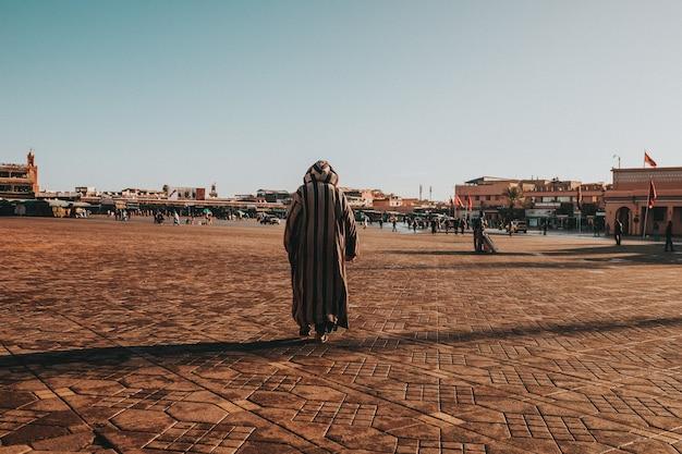 Nahaufnahme eines mannes, der unter blauem himmel in der stadt spazieren geht