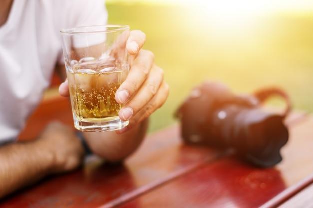 Nahaufnahme eines mannes hält ein glas bier.