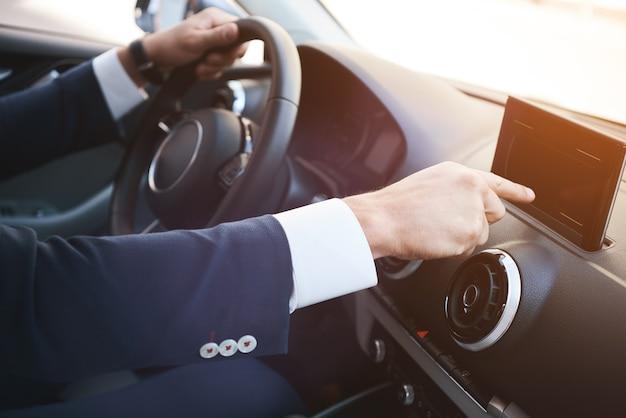 Nahaufnahme eines mannes hand touchscreen smartphone auf einem armaturenbrett
