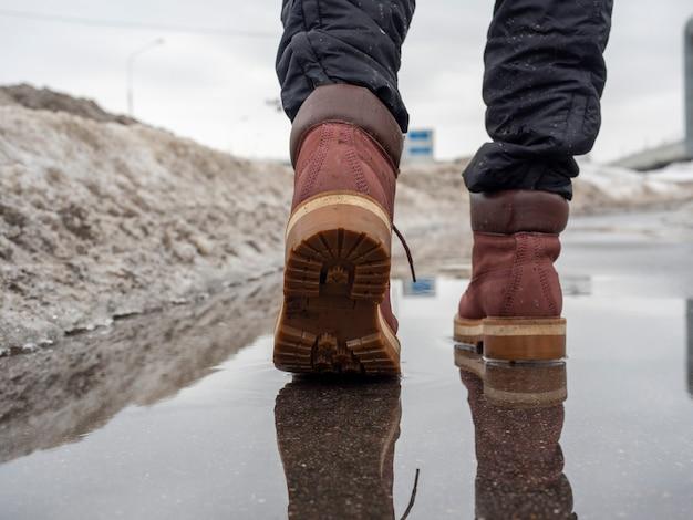 Nahaufnahme eines mannes in braunen schuhen, der im frühjahr auf nassem asphalt geht. schnee auf der ganzen straße