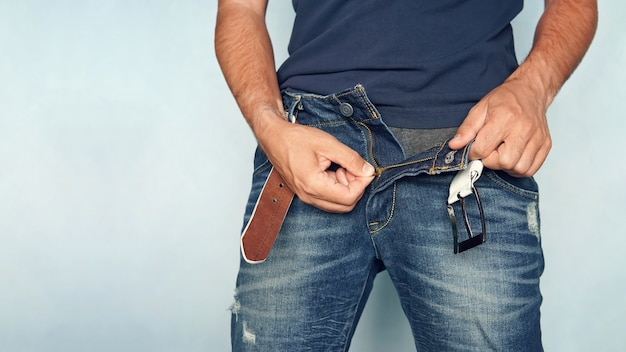 Nahaufnahme eines mannes in jeans mit offenem reißverschluss. aufgeknöpfte blaue hose