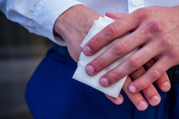 Nahaufnahme eines mannes mit einem antibakteriellen feuchten serviettentuch