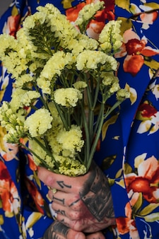 Nahaufnahme eines mannes mit tätowierung auf seiner hand, die in der hand limoniumblume hält