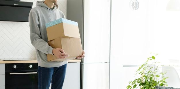 Nahaufnahme eines mannes mit umzugskarton, während das paar zusammen in ein neues zuhause ein- oder auszieht