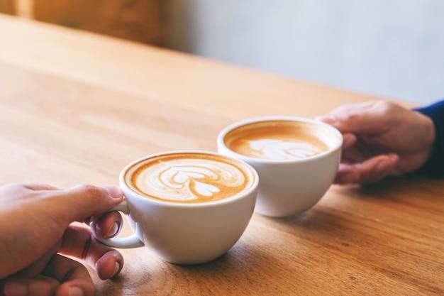 Nahaufnahme eines mannes und einer frau, die zwei kaffeetassen auf einem holztisch im café anstoßen?