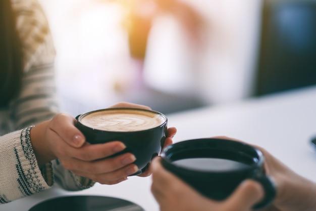 Nahaufnahme eines mannes und einer frau, die zwei kaffeetassen zusammenhalten