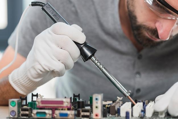 Nahaufnahme eines mannlötcomputerkreislaufs in der werkstatt