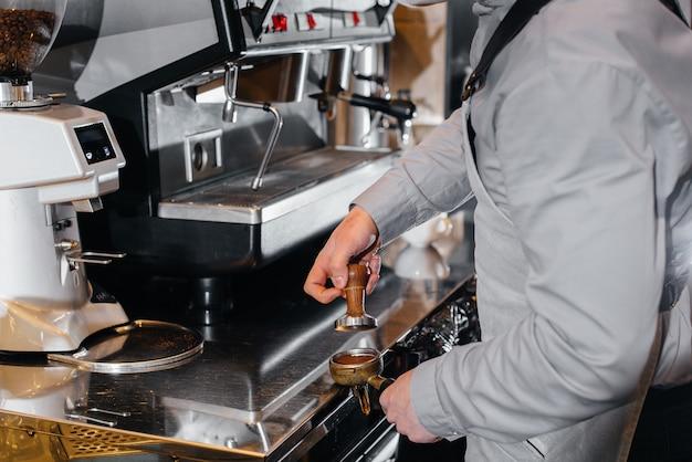 Nahaufnahme eines maskierten barista, der einen köstlichen kaffee an der bar in einem café zubereitet
