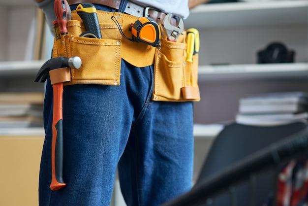 Nahaufnahme eines mechanikers, der einen werkzeuggürtel trägt, der sich auf die arbeit im innenbereich vorbereitet