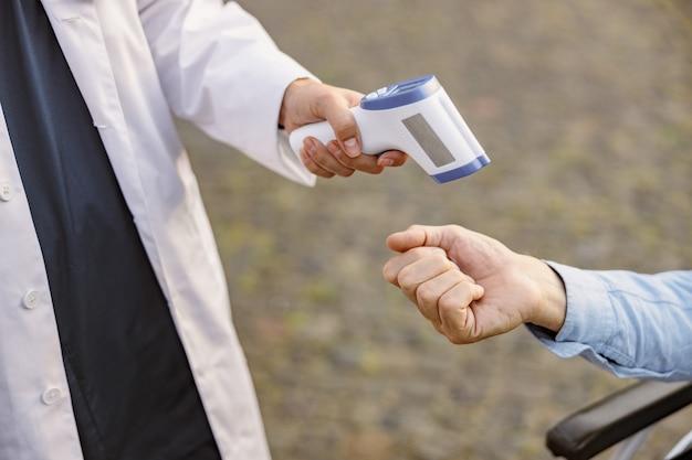 Nahaufnahme eines medizinischen infrarot-thermometers in einer hand des arztes, der die temperatur des mannes misst