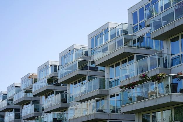 Nahaufnahme eines mehrfamilienhauses mit balkonen aus dem dorf. hintergrund der fenster und balkone eines mehrstöckigen glasgebäudes.