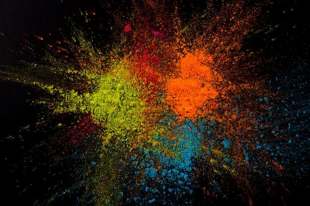 Nahaufnahme eines mehrfarbigen pulvers, das auf schwarzer oberfläche explodiert