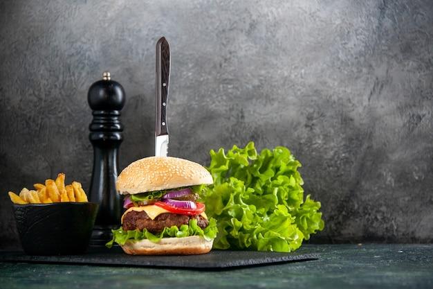 Nahaufnahme eines messers in leckerem fleischsandwich und grünen pommes auf schwarzem tablett auf grauer oberfläche