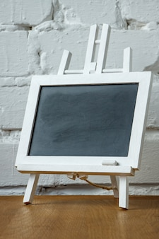 Nahaufnahme eines miniaturkreidebrettes mit kreideflecken und -kreide auf einer weißen backsteinmauer