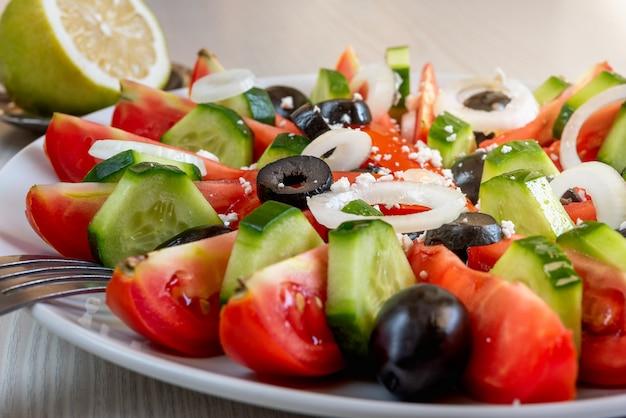 Nahaufnahme eines mit olivenöl beträufelten gemüsesalats aus gurken, tomaten und oliven