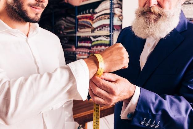 Nahaufnahme eines modedesigners, der das handgelenk seines kunden misst