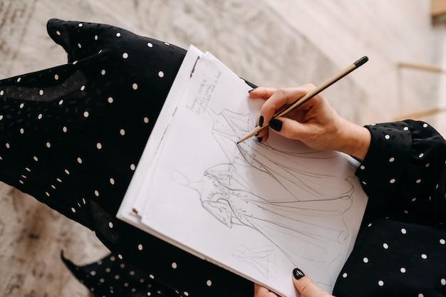 Nahaufnahme eines modehochzeitsdesigners, der neue brautkleider mit einem bleistift skizziert