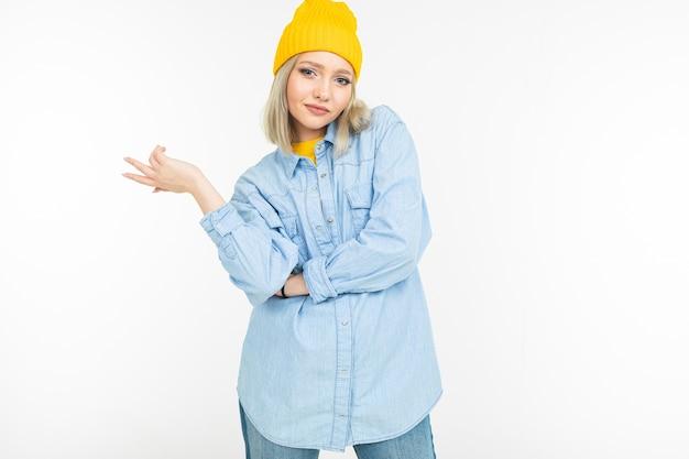 Nahaufnahme eines modellmädchens in einem stilvollen jeanshemd mit einem blonden haarschnitt auf einem weißen studiohintergrund. Premium Fotos