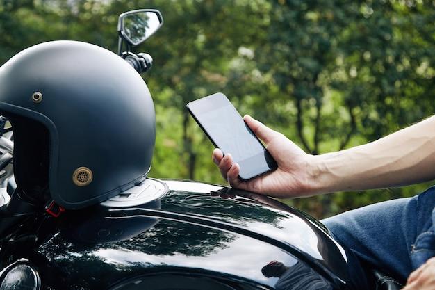 Nahaufnahme eines motorradfahrers, der auf dem fahrzeug sitzt und die anwendung auf dem smartphone überprüft