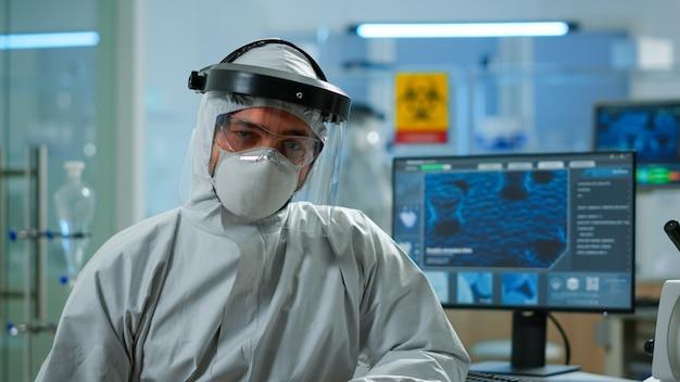 Nahaufnahme eines müden chemikers im overall mit blick auf die kamera, die im wissenschaftlichen labor arbeitet. wissenschaftler, der mit verschiedenen bakterien-, gewebe- und blutproben arbeitet, pharmazeutische forschung für antibiotika