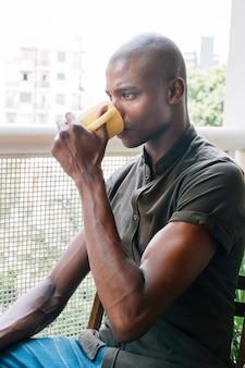 Nahaufnahme eines muskulösen jungen afrikanischen mannes, der den kaffee sitzt im balkon trinkt