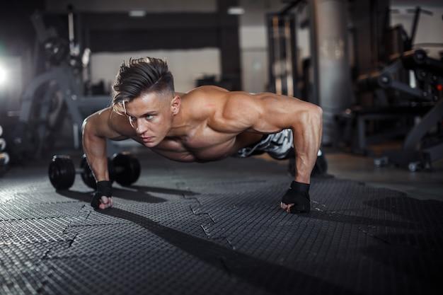 Nahaufnahme eines muskulösen jungen mannes, der gewichte im fitnessstudio auf dunklem hintergrund hebt. foto in hoher qualität
