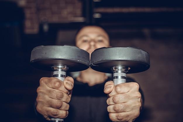 Nahaufnahme eines muskulösen jungen mannes, der gewichte im fitnessstudio auf dunklem hintergrund hebt.