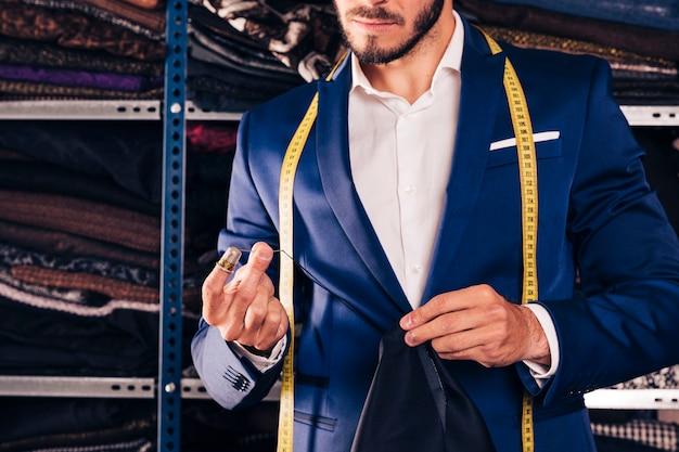 Nahaufnahme eines nähenden gewebes des männlichen modedesigners mit nadel in seiner werkstatt
