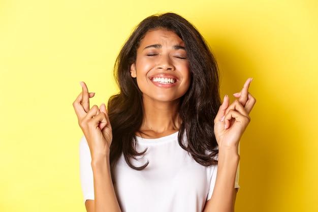 Nahaufnahme eines nervösen afroamerikanischen mädchens, das die finger für viel glück kreuzt und auf wichtige ergebnisse wartet, einen wunsch macht und auf gelbem hintergrund steht.