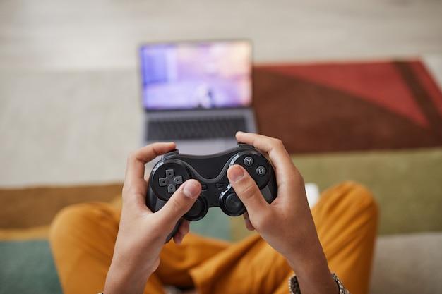 Nahaufnahme eines nicht erkennbaren afroamerikanischen jungen, der zu hause videospiele spielt, mit fokus auf händen, die gamepad halten, kopierraum