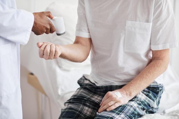 Nahaufnahme eines nicht erkennbaren arztes, der die temperatur des patienten im krankenzimmer überprüft und das infrarot-thermometer zur hand zeigt