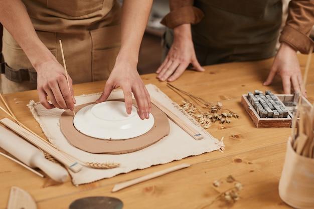 Nahaufnahme eines nicht erkennbaren männlichen handwerkers, der keramik in der töpferwerkstatt herstellt, kopierraum